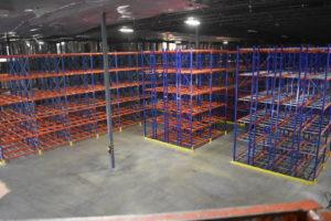 An empty warehouse full of racking shelves.