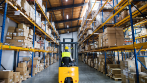 An employee driving a forklift in a warehouse.