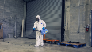Person in a hazmat suit spraying a warehouse.