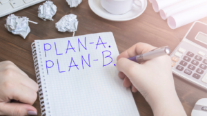An employee writing Plan A and Plan B on a notebook.