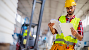 Employee reviewing plans in a warehouse.